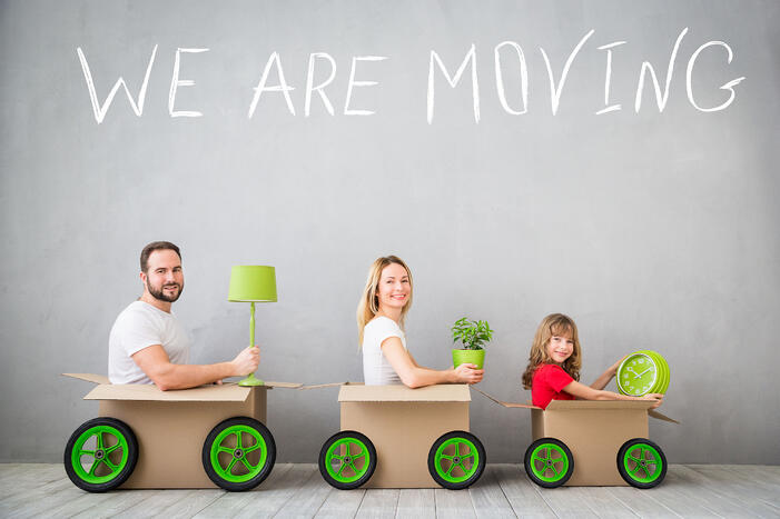 """Parents and child sitting in boxes with the text """"We are moving"""" above them."""