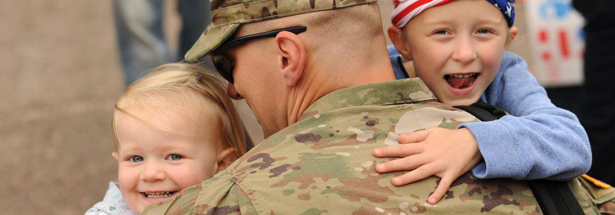 Male soldier holding his two children.